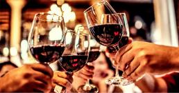 5 personen die met hun glazen rode wijn proosten
