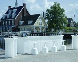 Lange witte Ibiza bara met krukken en twee statafels van het zelfde materiaal