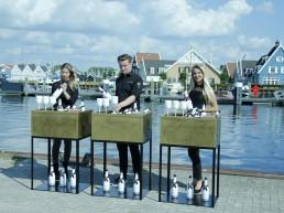3 gouden bars met daarachter 3 bar medewerkers die champagne serveren