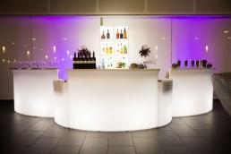 Mooie witte half ronde bar met drankflessen en ijskoelers verlicht met led lampen