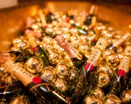 een gouden badkuip gevuld met flesjes Moet & Chandon champagne met gouden kerstballen