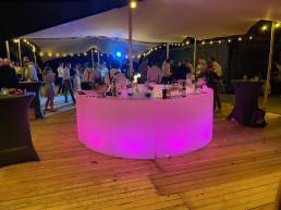 Ronde led bar in de kleur roze op een houten vloer onder een tent op een bruiloft feest