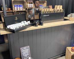 Zwarte bar met eiken blad en een dakje met koffie decoratie en een koffie machine