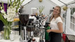 witte bar met bloemen en een koffie machine met een barista