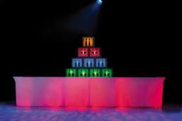 Lange rood gekleurde bar met daarachter gekleurde blokken en een lamp